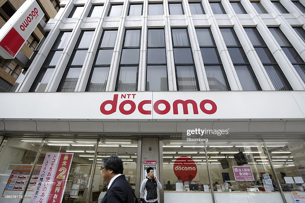 A man speaks on his mobile phone outside an NTT Docomo Inc store in Tokyo Japan on Thursday April 24 2014 Docomo plans to sell a stake in Tata...