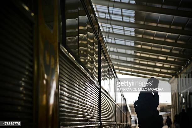 A man speaks on the phone near a train at Santa Apolonia train station in Lisbon on March 13 2014 REFER National Railways Company and CP Portugal...
