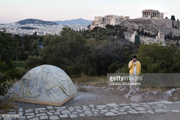 A man speaks on the phone next to an installation by Canadian artist Rebecca Belmore a tent in marble symbolising the refugee crisis in Greece and...