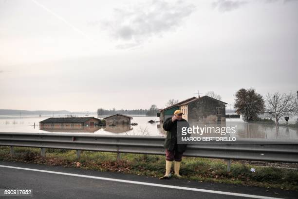 A man speaks on the phone next to flooded fields on December 12 2017 in Brescello The Civil protection authority is evacuating about a thousand...