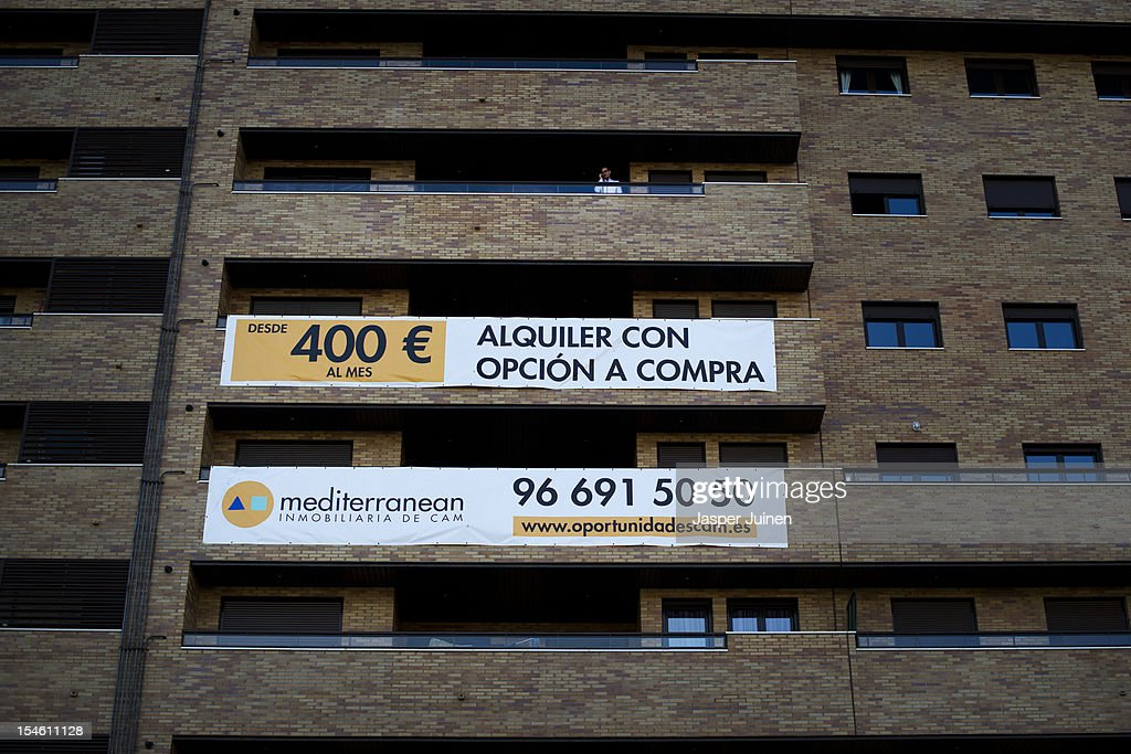 A man speaks on the phone while standing on the balcony above an appartment offered from 400 Euro's a month, with an option to buy, on October 22, 2012 in Sesena, Spain. With a housing backlog of more than 1.2 million unsold newly build homes, banks in Spain have recenlty started to sell their real estate assets with discounts, some upto 80 percent, slashing prices to a level not seen for over 20 years. With morgages of 100 percent, some experts worry that mistakes from the past are repeated again.