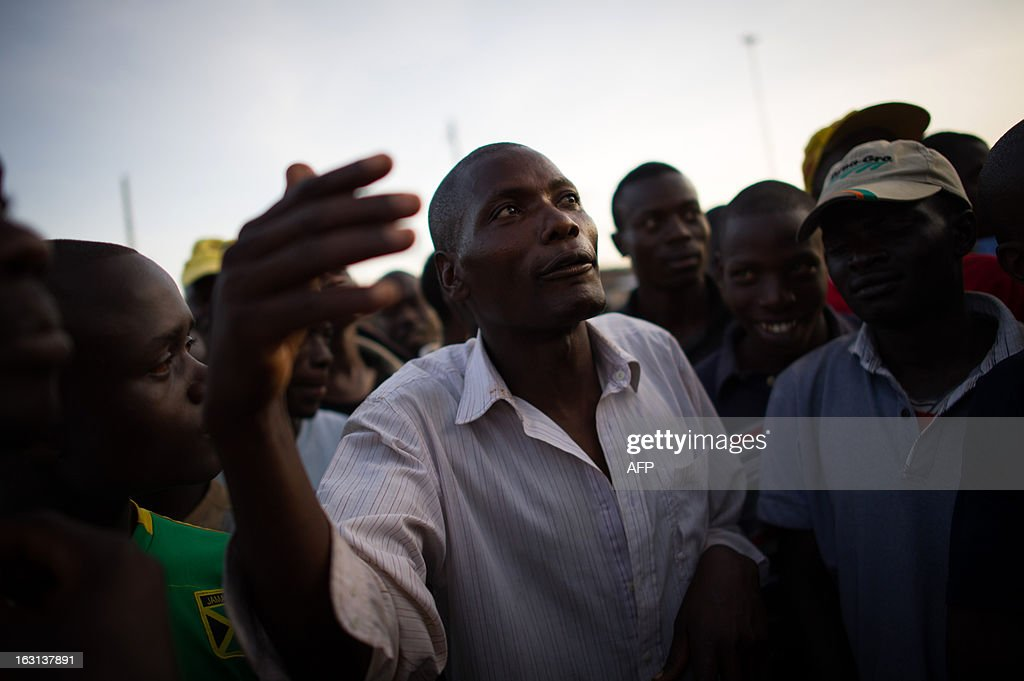 A man speaks to a crowd of people as residents of the Kibera slum in Nairobi discuss the incoming election results in the Kenyan capital on March 5, 2013. Kenya's deputy prime minister Uhuru Kenyatta, who faces an international crimes against humanity trial, took an initial lead in presidential elections today, the first since disputed polls five years ago sparked a wave of violence.