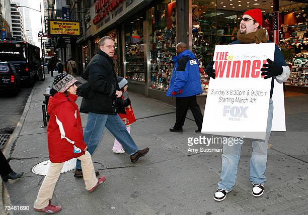 A man speaks to pedestrians as he wears a sign promoting Rob Corddry's new show The Winner on Fox held at Times Square on March 1 2007 in New York...