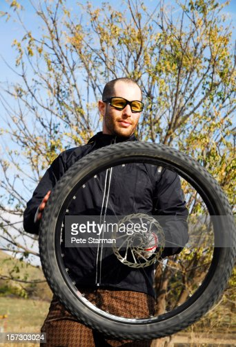 Man spinning a bike wheel in his hand : Stock Photo