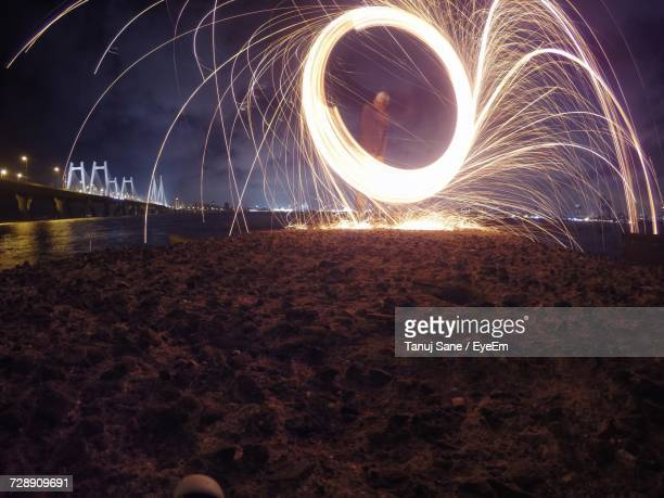 Man Spinning Wire Wool On Rock Formation At Sea Shore During Night