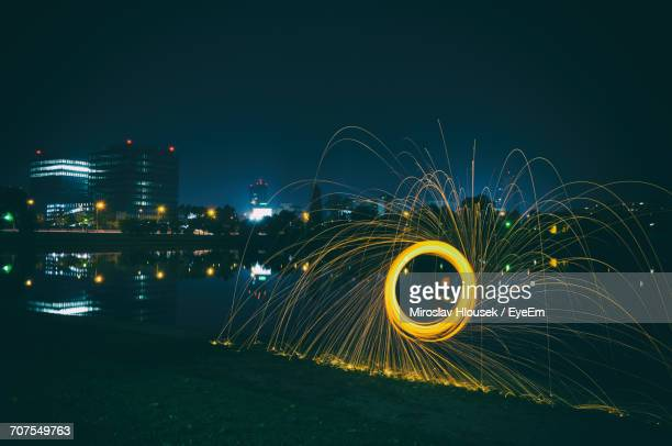 Man Spinning Wire Wool While Standing Against River In City