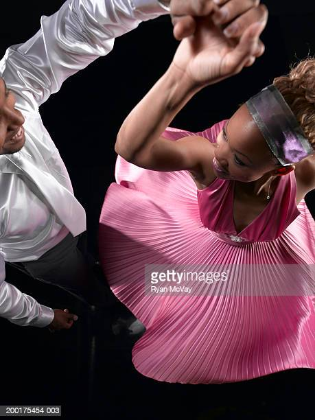 Man spinning woman on dance floor, elevated view