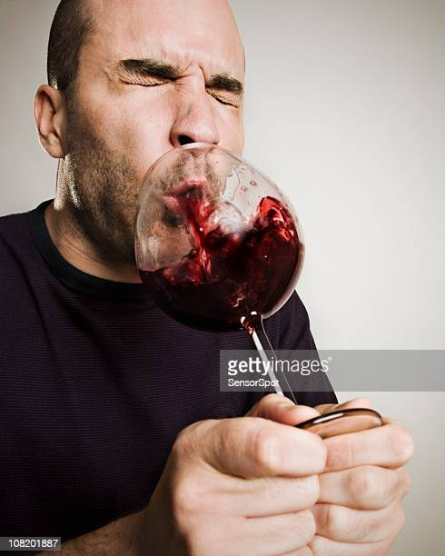 Mann Spucken zurück in ein Glas Wein