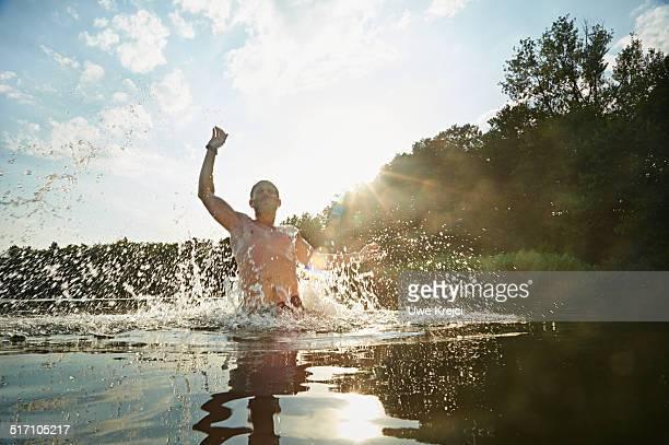 Man splashing water in lake