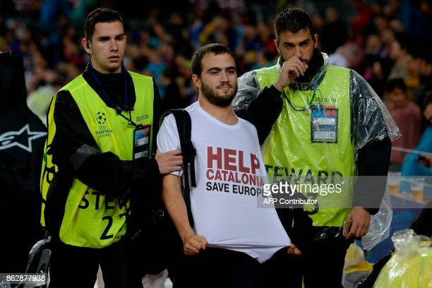 A man sporting a tshirt demanding help for Catalonia is taken out the field by security personnel during the UEFA Champions League group D football...