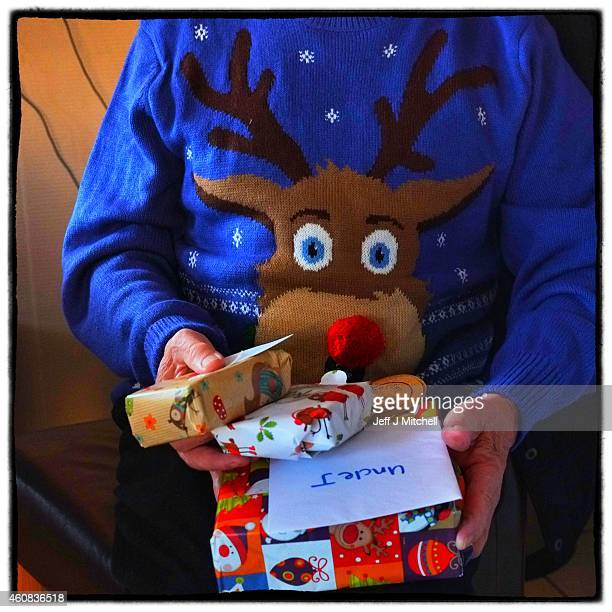 A man sports a Christmas jumper while opening Christmas present on December 25 2014 in Glasgow Scotland Millions of people across the UK spend time...