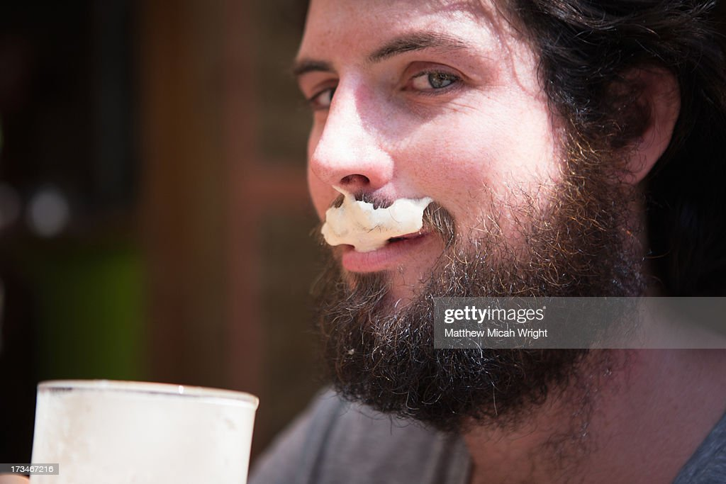 A man sports a milk moustache from coffee : Stock Photo