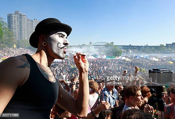 A man sports a painted face as he smokes marijuana as thousands of people gather at 4/20 celebrations on April 20 2016 at Sunset Beach in Vancouver...