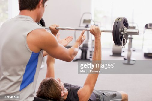 Man spotting friend lifting barbell in gymnasium : Stock Photo