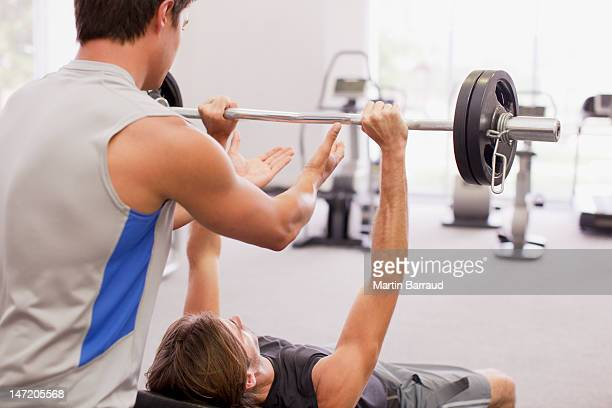 Man spotting friend lifting barbell in gymnasium