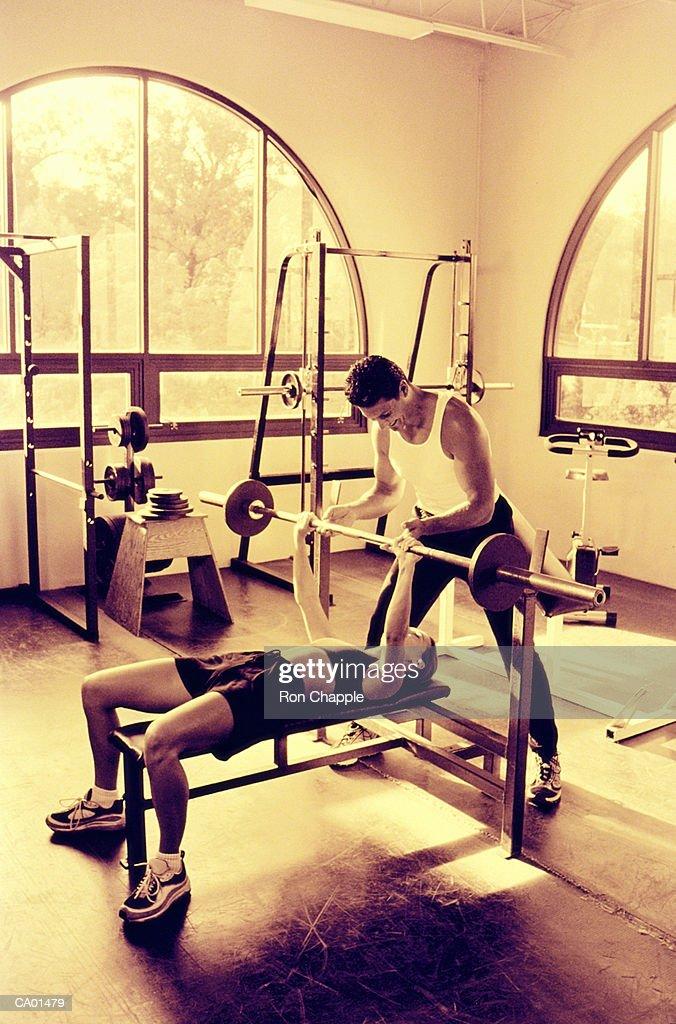 Man spotting woman doing bench press in gym (Toned B&W) : Stock Photo