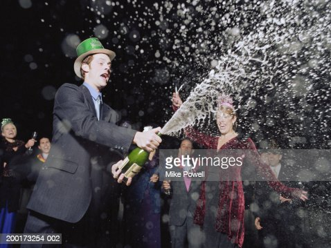 Man spraying champagne at New Years Eve party : Stock Photo