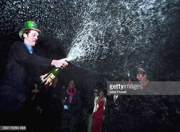 Man spraying champagne at New Years Eve party