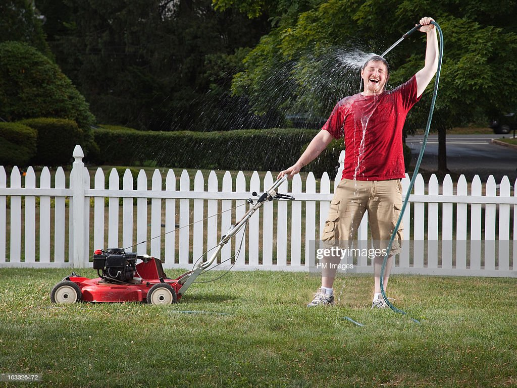 Man spraying himself with hose : Stock Photo