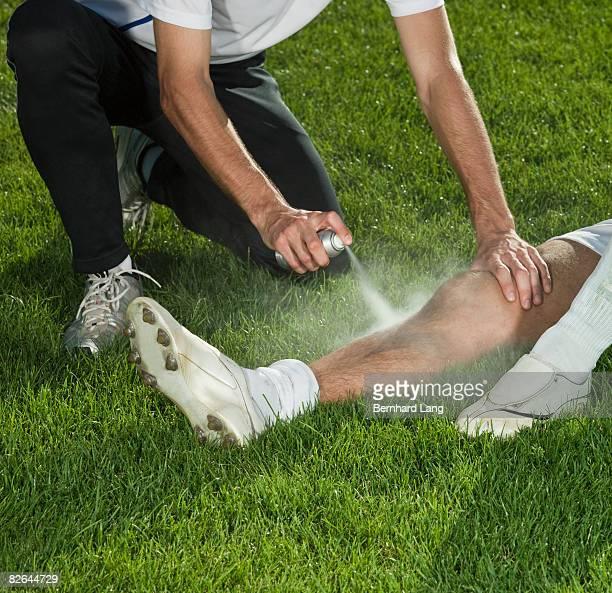 Man spraying leg of soccer player