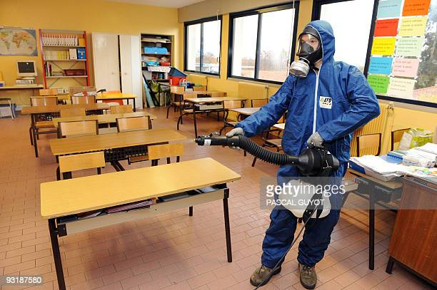 A man sprays a disinfectant against the swine flu virus on November 18 2009 in a classroom of the Georges Brassens school in Baillargues southern...