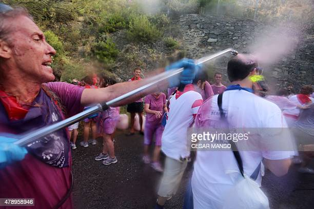 A man sprays red wine on revellers during the'Batalla del Vino' in Haro on June 29 2015 Every year thousands of locals and tourists climb a mountain...