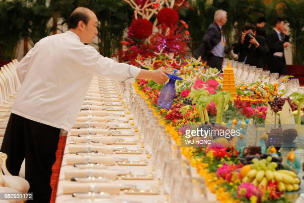 A man sprays water on the table prepared for heads of states before the welcoming banquet of the Belt and Road Forum in Beijing's Great Hall of the...