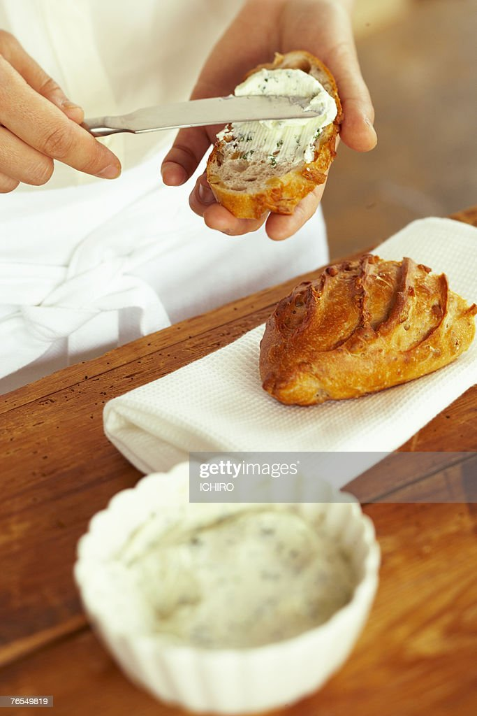 Man spreading creamy dip on bread, mid section : Stock Photo