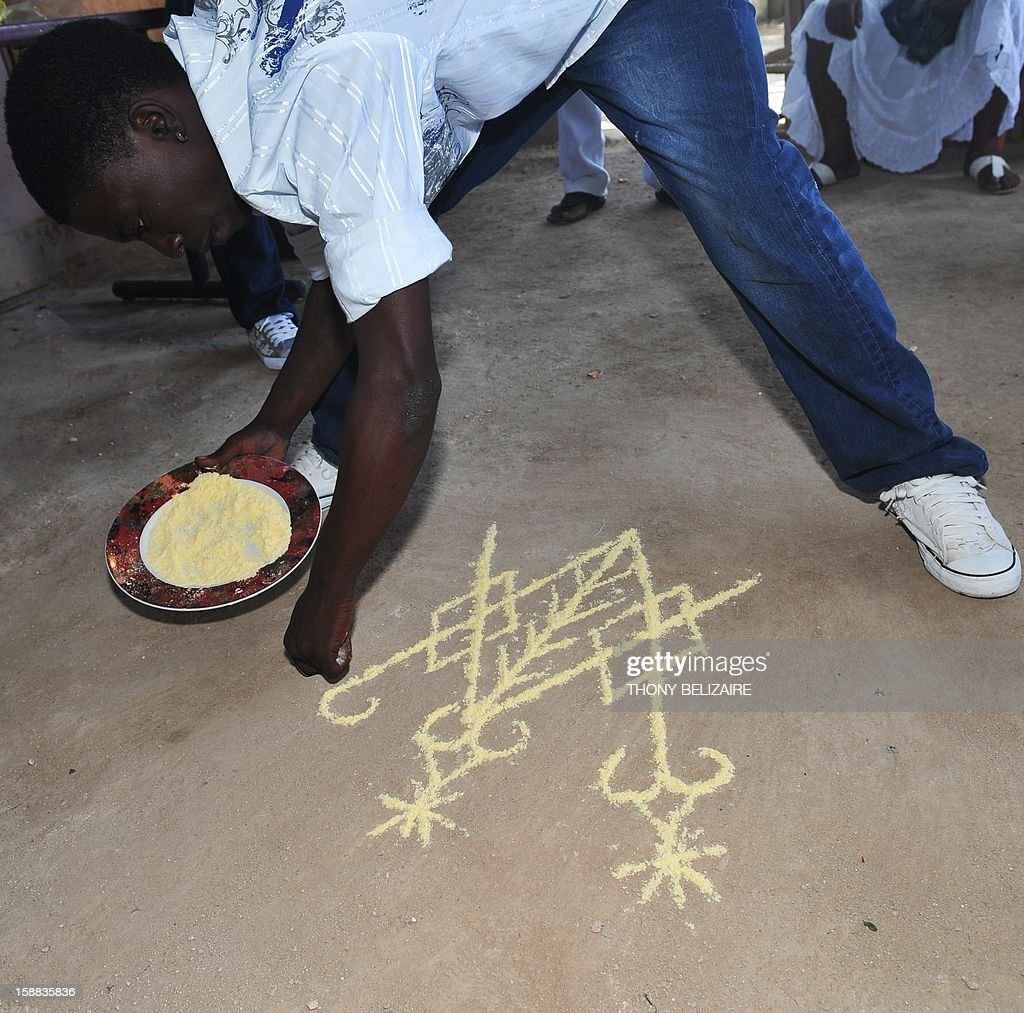 A man spreads corn meal for good luck as he takes part in a Voodoo ceremony December 30, 2012 in the Petion-ville suburb of Port-au-Prince. The Haitian government declared Voodoo an official religion in 2003, granting Voodoo priests the authority to perform weddings and baptisms. AFP PHOTO/Thony BELIZAIRE