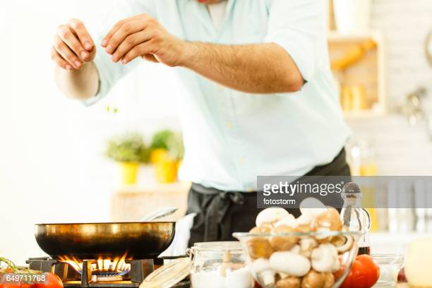 Man sprinkling seasoning, cooking dinner