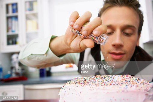 Man Sprinkling Sprinkles on Cake