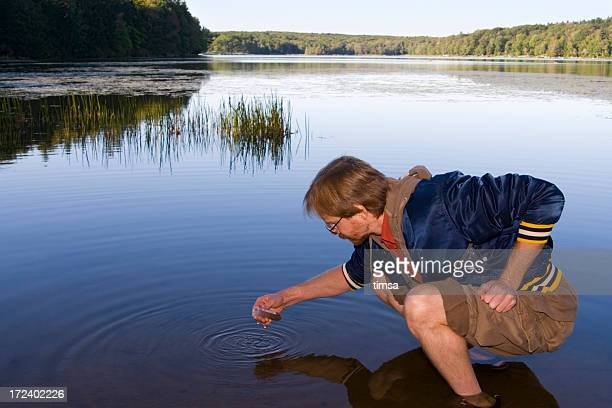 Man squatting collecting a sample from water