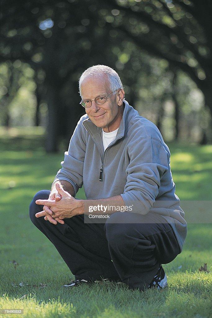 Man squatting : Stock Photo