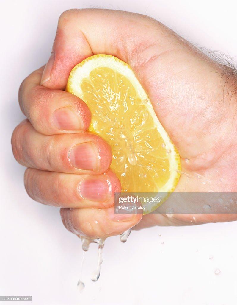Man squeezing cut lemon in fist, close-up