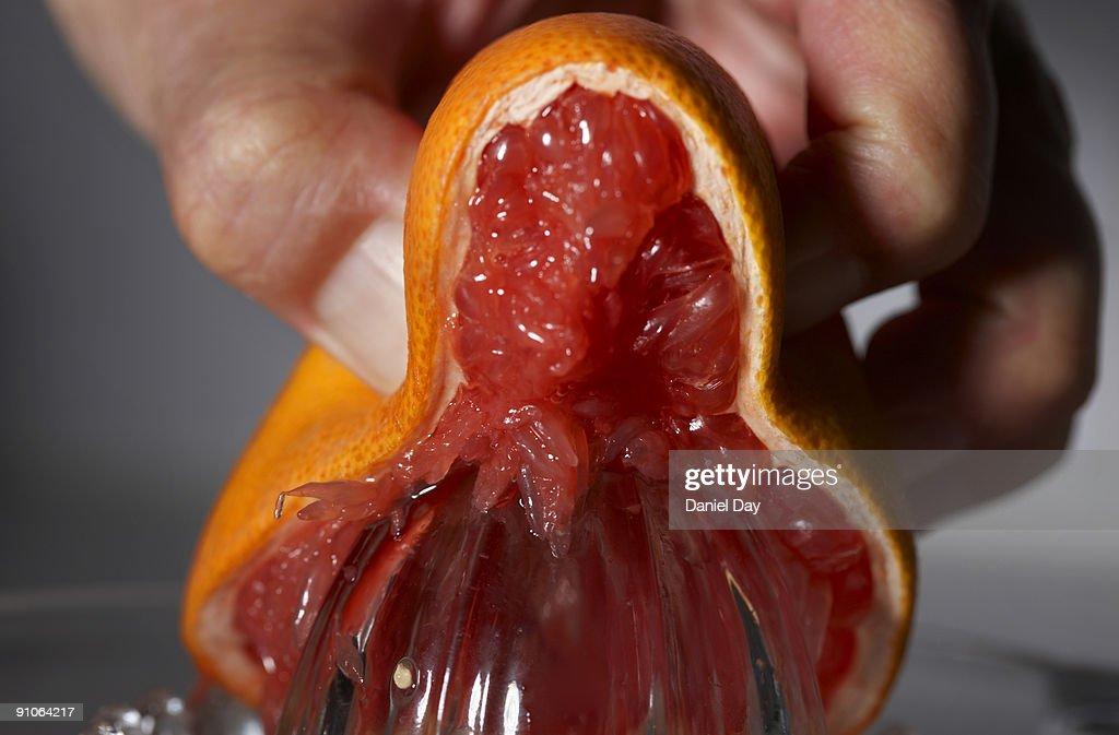 man squeezing grapefruit : Stock Photo