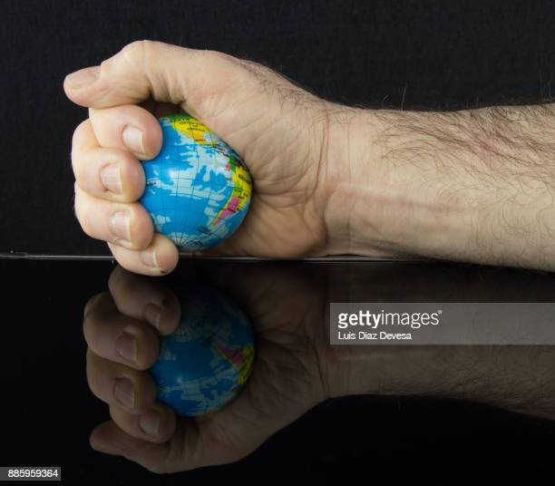 Man squeezing therapy ball shaped like planet earth