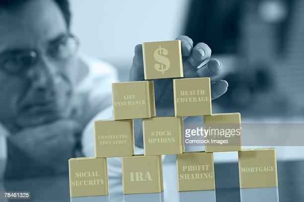Man stacking blocks of money matters