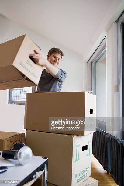 Man stacking cardboard boxes in house