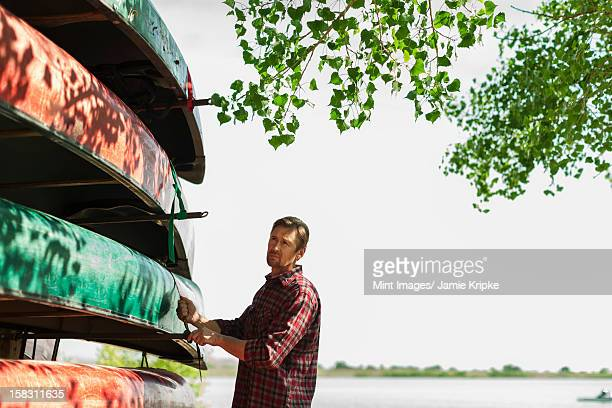 A man stacking narrow rowing boats and lashing them onto a trailer or stand.