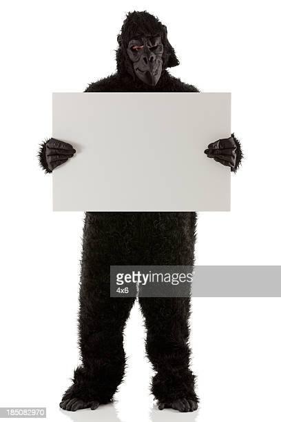 Homem stading em Fantasia de gorila com uma Placa de manifestação