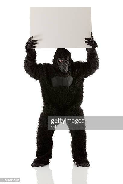 Man stading in gorilla costume with a placard
