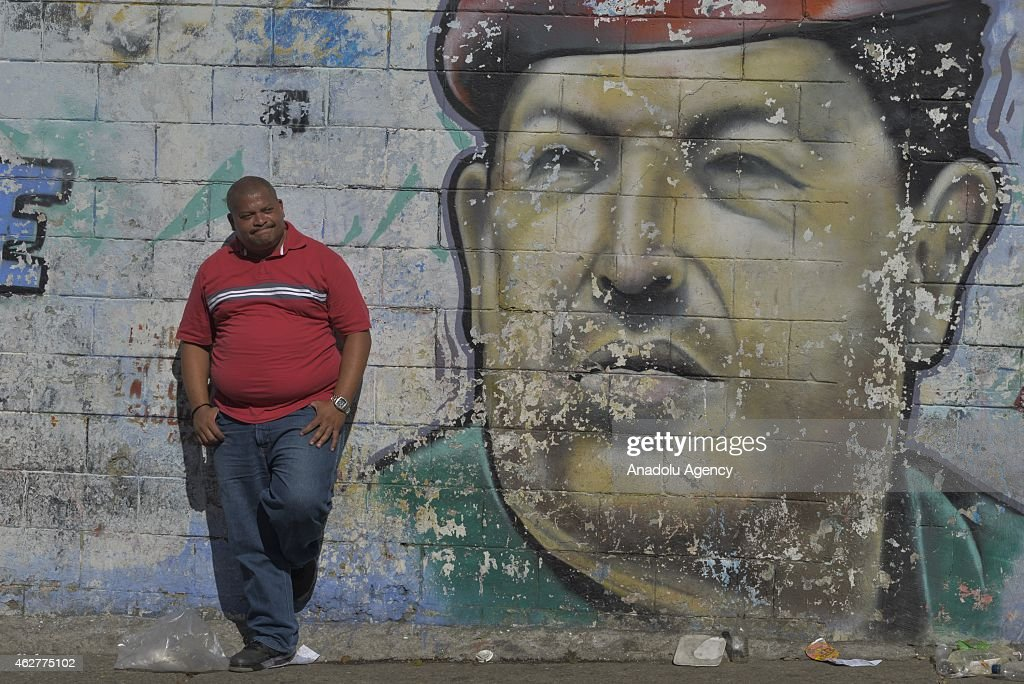 A man stand by a wall Hugo Chavez image painted during a military parade for the 23rd anniversary of attempted coup of Hugo Chavez against Carlos...
