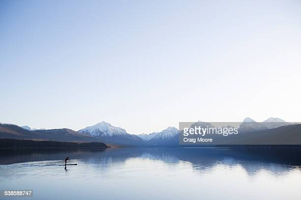 A man stand up paddle boards (SUP) on a calm Lake McDonald in Glacier National Park.
