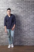 handsome man stand with brick wall, asian