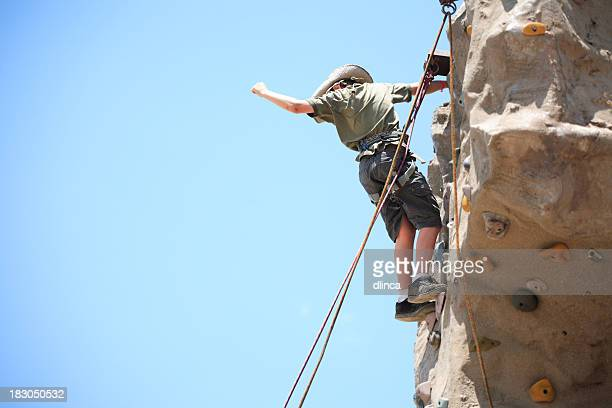 Man standing almost to the top of a rock climbing face