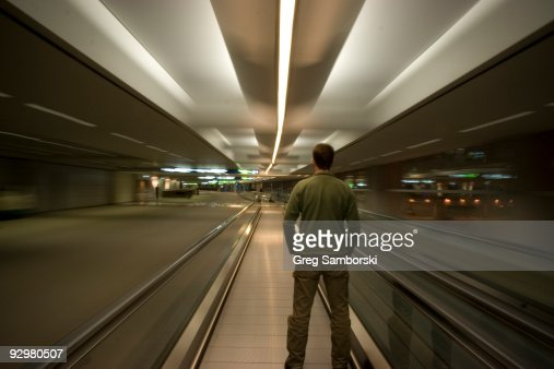 Man standing alone on moving airport walkway