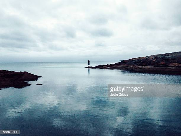 Man standing alone on rocks looking out at ocean