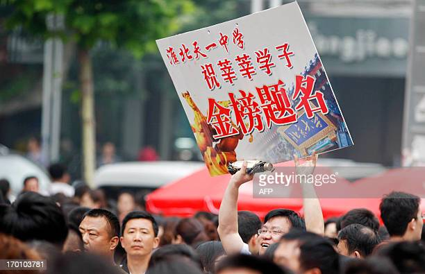 A man standing amongst parents holds a banner wishing students good luck during their 2013 university entrance exam in Huaibei east China's Anhui...