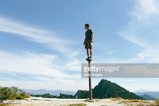 A man standing and balancing on a metal post,looking towards expansive sky,on Surprise Mountain,Alpine Lakes Wilderness,Mt. Baker-Snoqualmie national forest.