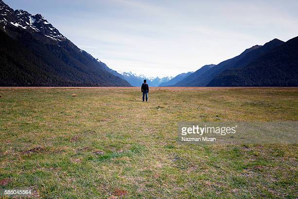 A man standing and facing towards vast empty landscape.